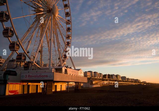 Brighton ferris wheel and Kemptown seafront illuminated by the rising sun - Stock Image
