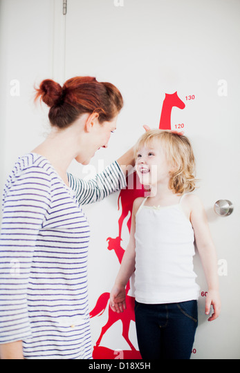 Mother measuring daughters height on height chart - Stock Image