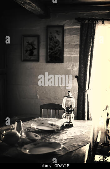 old cottage room with the table ,lamp,plates - Stock Image