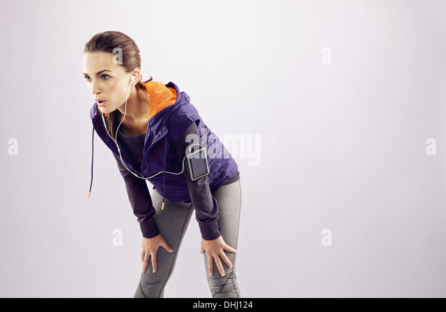Young female runner with hands on knees. Tired young woman resting after jogging on grey background with lots of - Stock Image