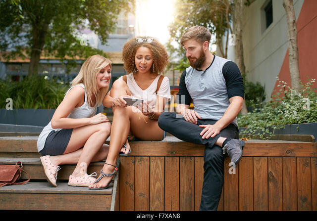 Outdoor shot of group of young adults looking at cellphone. Young friends using mobile phone. - Stock Image