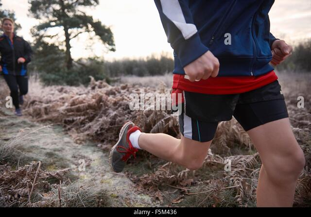 Cropped low angle view of mother and son jogging on frosty grassland - Stock Image