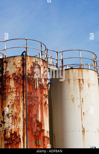 Corroded and corroding chemical storage vessels in a chemical plant complex - Stock Image