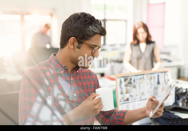 Fashion designer using digital tablet and drinking coffee in office - Stock Image