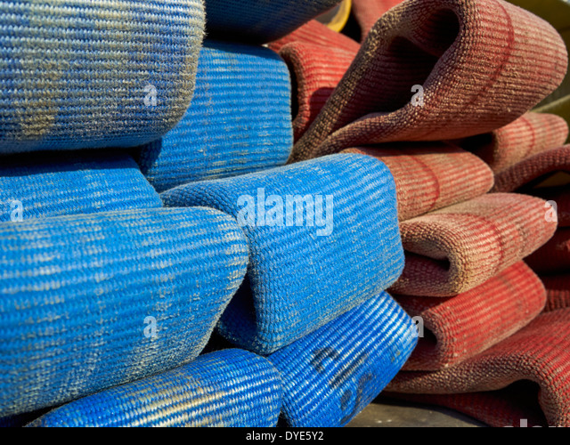 blue and orange fire hoses coiled on a firetruck - Stock Image