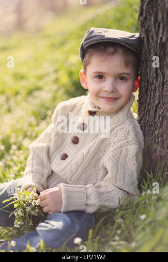Boy leaning against a tree trunk, holding bunch of spring flowers - Stock Image