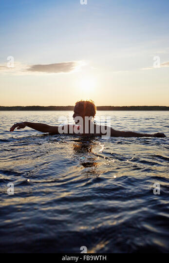 Sweden, Vastra Gotaland, Skagern, Woman swimming in lake - Stock Image