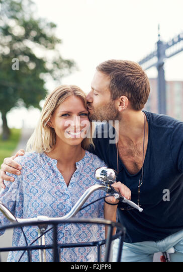 Affectionate young man kissing his girlfriend on the forehead as they enjoy a summer day in the fresh air on their - Stock-Bilder