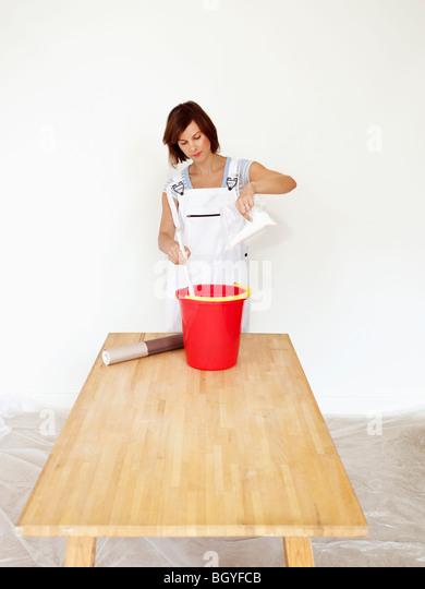 Woman mixing wallpaper glue - Stock Image