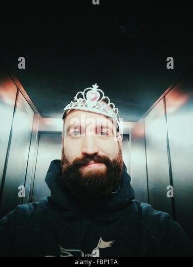 Portrait Of Man Wearing Crown In Elevator - Stock-Bilder