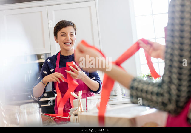Smiling female caterers wrapping baked goods in boxes with red ribbon in kitchen - Stock-Bilder