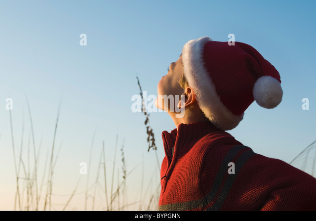Boy wearing Santa hat outdoors, contemplatively looking away - Stock Image