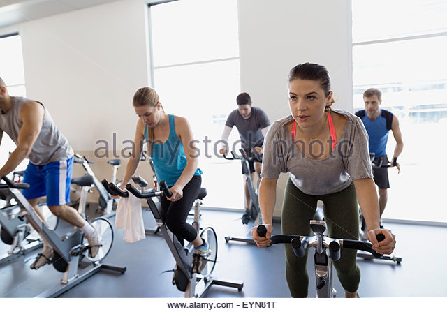 Spin class on stationary bikes at gym - Stock-Bilder