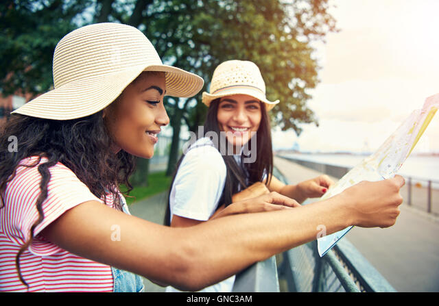 Woman in overalls and smiling reads a map while her happy friend stands nearby - Stock Image