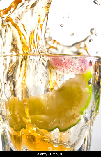 Tequila Splash with Motion and Lime - Stock Image