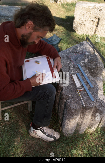 Greece Olympia first Olympic games in 776 B.C. male archaeologist measures cornerstone - Stock Image