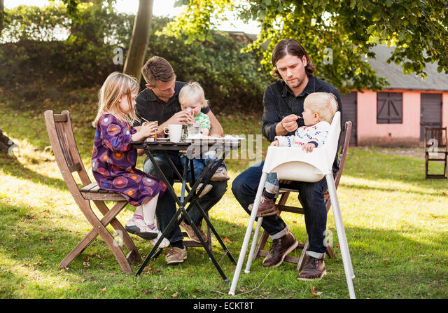 Full length of men feeding children in park - Stock Image