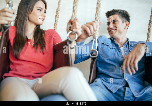 Young couple relaxing in swing while talking and flirting - Stock-Bilder