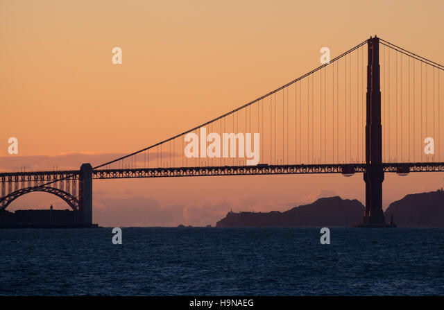 A silhouetted Golden Gate Bridge at sunset in San Francisco, California. - Stock Image