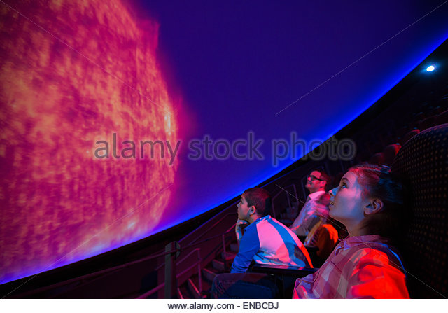 Students watching planet at planetarium show - Stock Image
