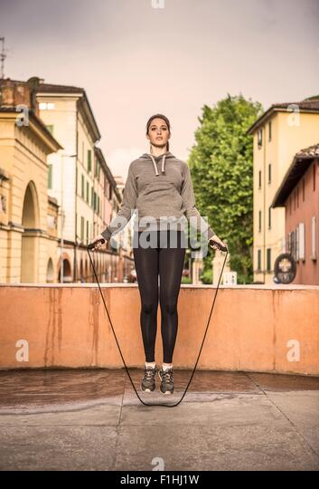 Front view of woman wearing sports clothes using skipping rope - Stock Image