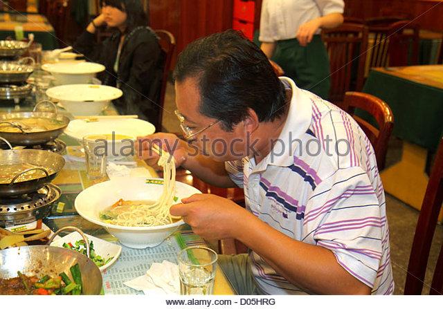 China Shanghai Huangpu District Sichuan Road restaurant food Asian man chopsticks noodles eating dining - Stock Image