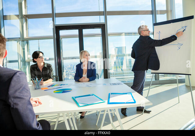 Senior architect giving presentation in business meeting - Stock Image