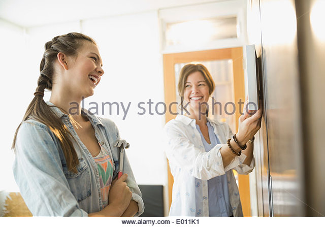Mother and daughter hanging picture frame on wall - Stock Image