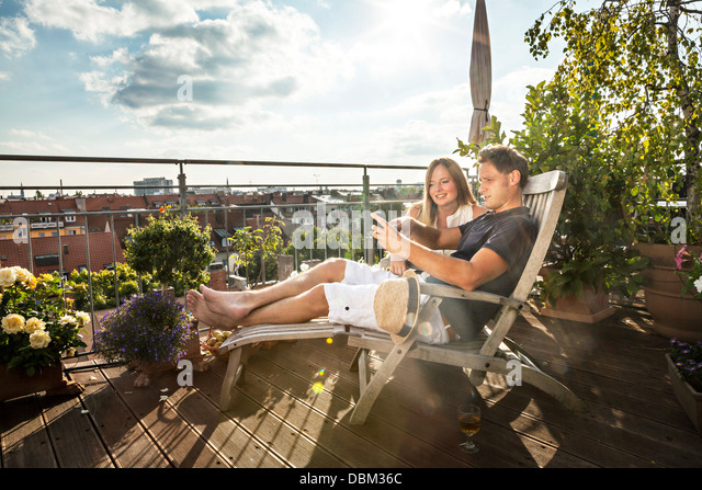 Couple On Balcony Using Mobile Phone, Munich, Bavaria, Germany, Europe - Stock Image
