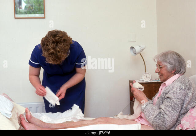 District nurse changing dressing on elderly woman's leg ulcer - Stock Image