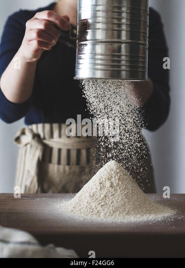 Sieving flour, ready for baking. - Stock Image