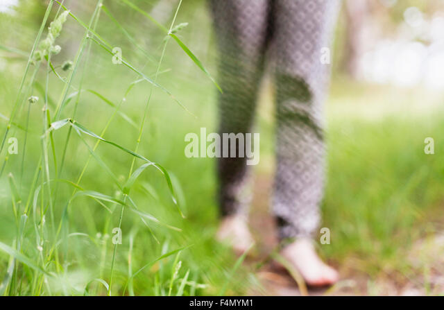 Low section of woman walking on grassy field - Stock Image