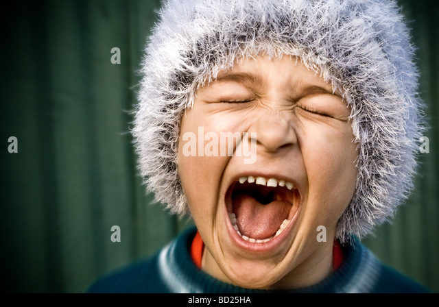 Close up of portrait of crazy kid screaming loudly - Stock Image