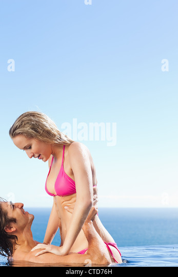 Man elevating his girlfriend in the pool - Stock Image