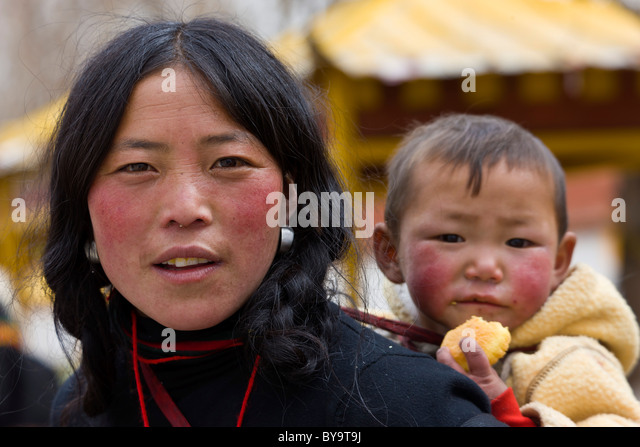 Tibetan woman with child in papoose on her back Norbulingka or Jewel Park, Tagten Migyur Podrang, Lhasa, Tibet, - Stock Image