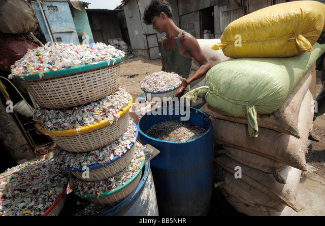 Baskets of plastic chips being washed by young Indian worker in Dharavi slums - Stock-Bilder