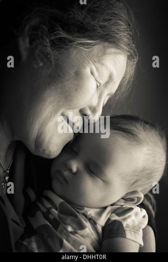 Portrait of grandmother holding baby granddaughter - Stock-Bilder