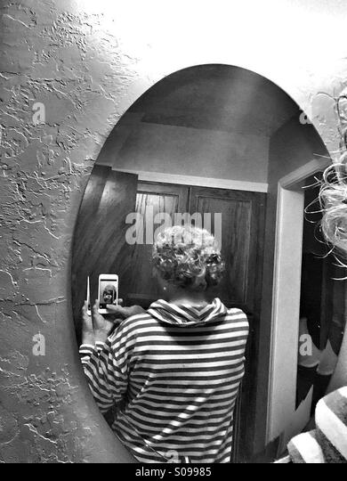 An older Caucasian woman takes a cell phone photo of the back of her hair using a mirror. - Stock Image