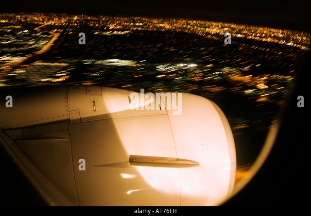 Fuselage engine over blur lights of a city as it lands - Stock Image