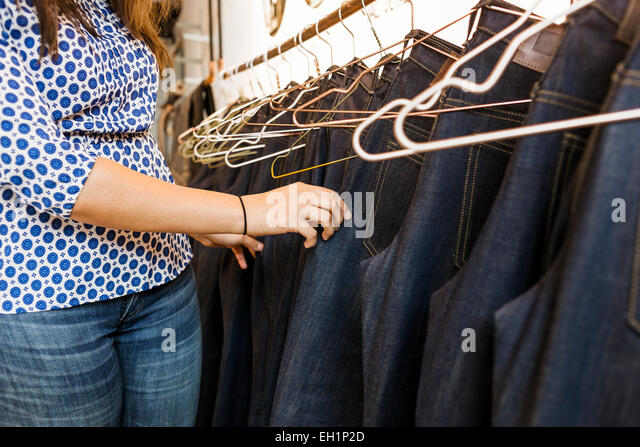 Midsection of woman choosing jeans in factory - Stock Image