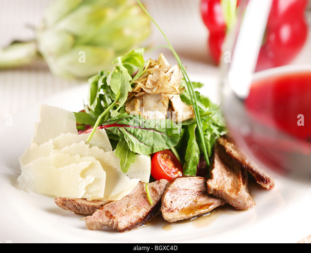 salad with pork, tomatoes and arugula on a white plate - Stock Image