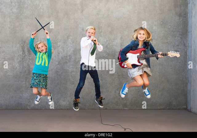 Sisters and brother rocking out - Stock-Bilder