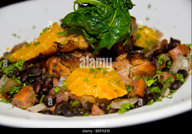 Broiled chicken with black beans, sausage, spinach and orange slices white plate food detail closeup San Antonio - Stock Image