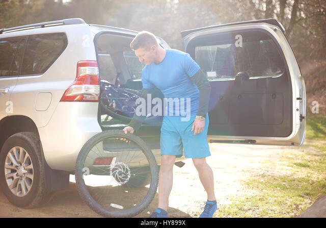 A man prepares to go mountain biking - Stock Image