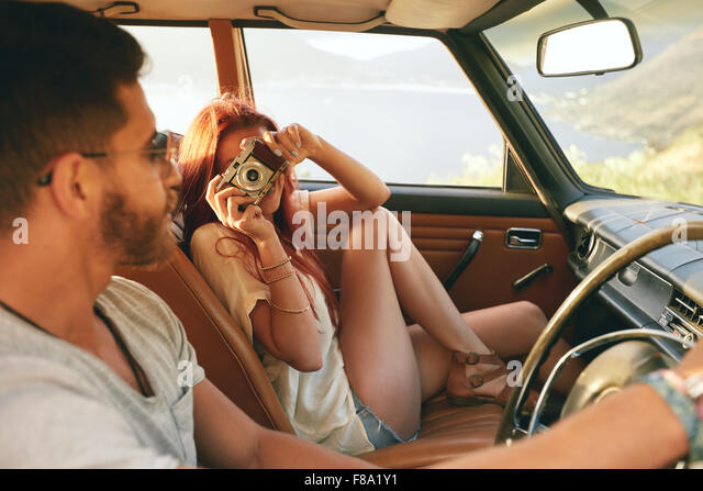 Caucasian couple going on a road trip. Woman taking pictures with camera and man driving car. - Stock Image