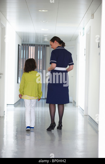 Nurse and young girl walking in corridor - Stock Image