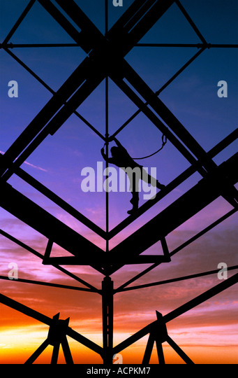 Steelworker silhouetted against dramatic sunset sky. - Stock-Bilder