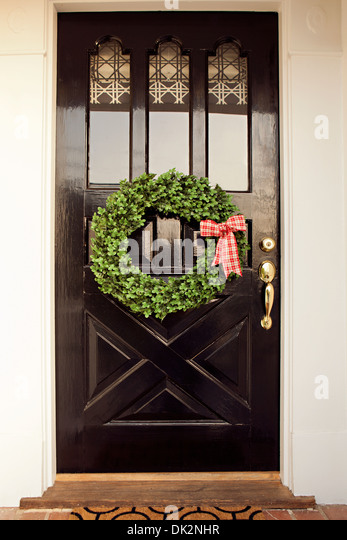 Red and white gingham ribbon on Christmas wreath hanging from black front door - Stock Image