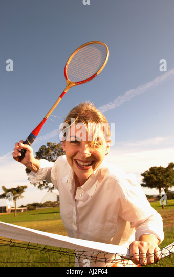 A woman plays badminton in a park - Stock Image