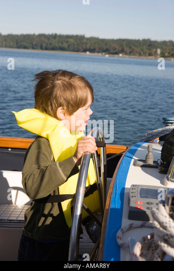 A boy steering a boat - Stock-Bilder